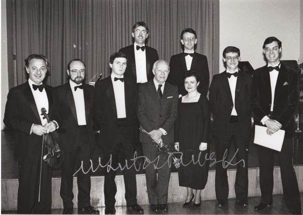 Witold Lutosławski at a concert of his chamber music in the Harty Room of Queen's University, Belfast, on 17 December 1987.From left to right: György Pauk (violin), Donal McCrisken (piano), Damian Frame (clarinet), Francis King (piano), Lutosławski, Colin Stark (oboe), Jacqueline Horner (mezzo-soprano), John O'Kane (cello) and Roger Vignoles (piano)
